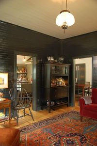 Windsor chair, rug, velvet chair and high gloss Black walls. Black wall paint gives this traditional room an instant edge.