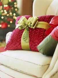 Buy pillows in holiday colors and then wrap them with ribbon!