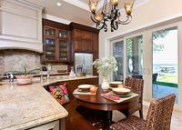 This traditional kitchen has a view of the beach and features an L-shaped island and built-in banquette.