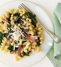 Cellentani Pasta with Ham and Kale ~ saucy one-dish pasta recipe topped with grated Romano cheese.