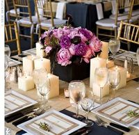 Square chargers and square candles surrounded a square vessel containing cabbage roses, peonies and begonia foliage. The shape of these details echoed the table�€˜s shape, while woven raffia runners added a natural feel.