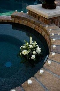 floating flowers and candles surrounding pool